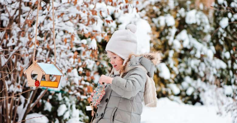 Pige fodrer fugle ved fuglebræt om vinteren